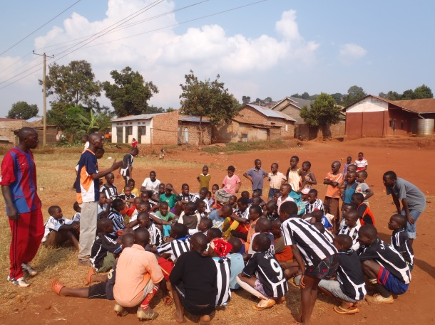 Coach Richard addressing the youth of Kireka (outside Buwate).  Donations from the Bobby Robson foundation can be seen on many of the children.