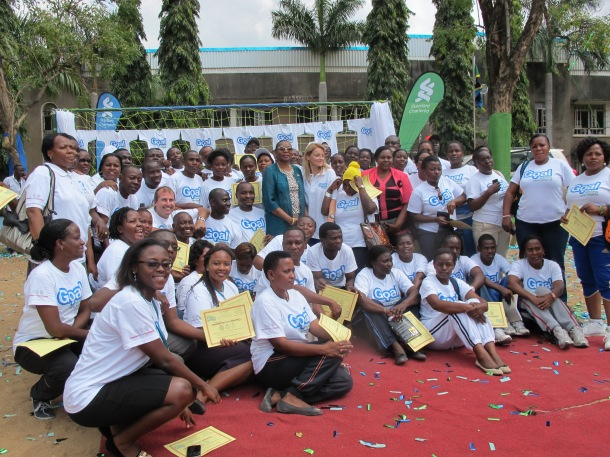 Teachers and coaches pose alongside the guests of honor with their certificates.